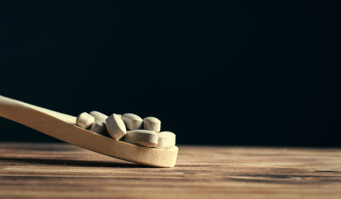 supplements on a wooden spoon